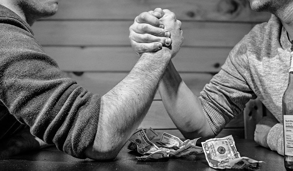 Arm-wrestling over money.