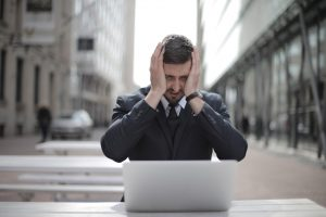 Man in suit covering his face and looking at a computer